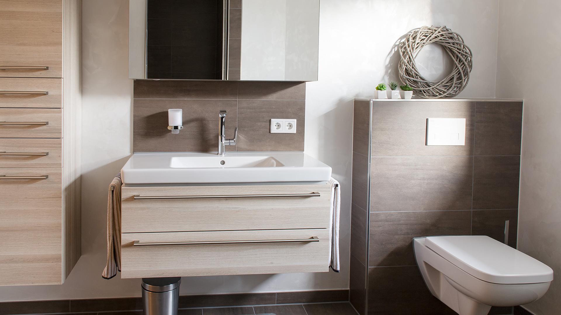 Schöner heller Waschtisch und Toilette an braun gefliester Wand