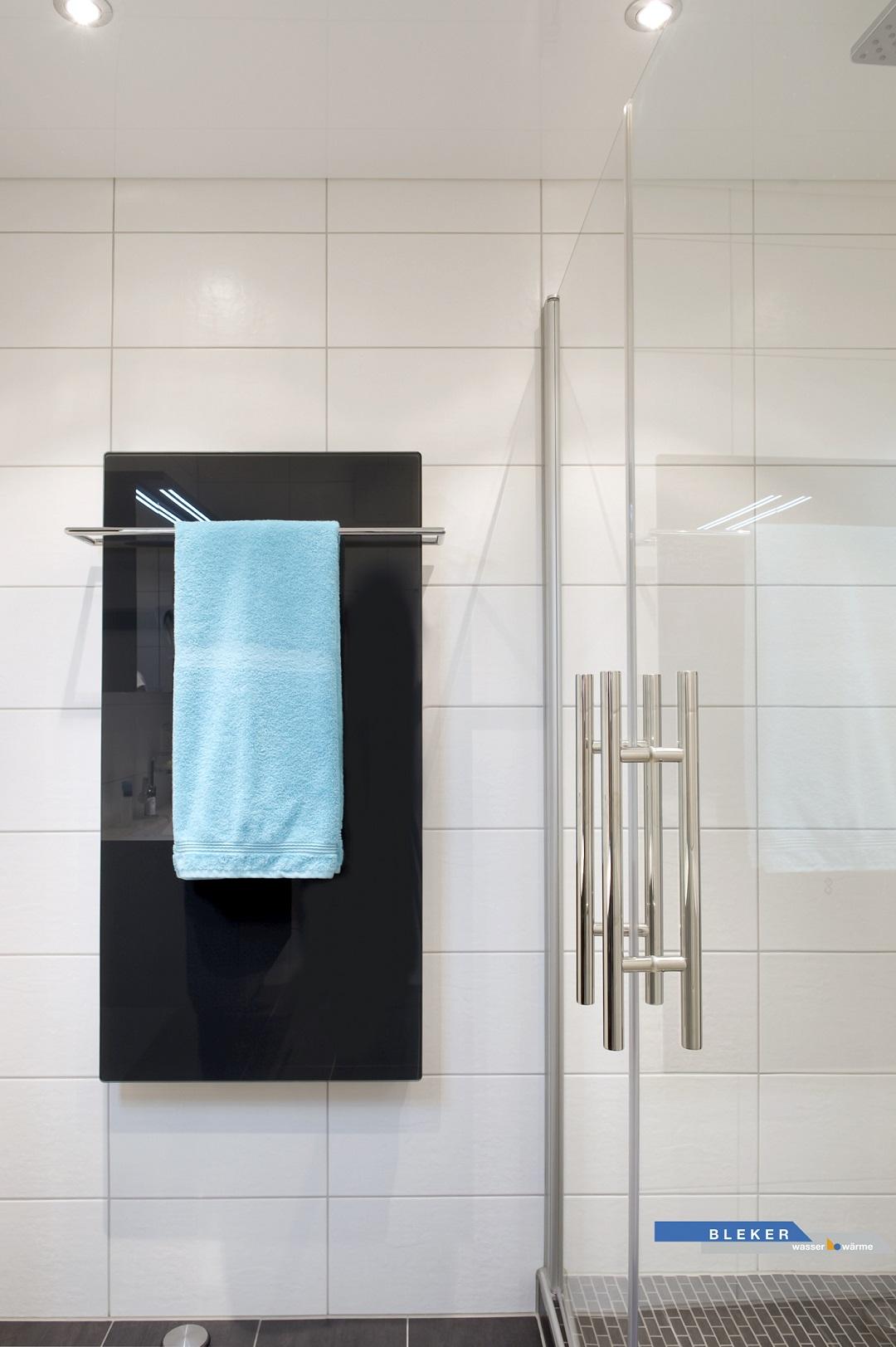 schwarzer glänzender Handtuchheizkörper und türkises Handtuch