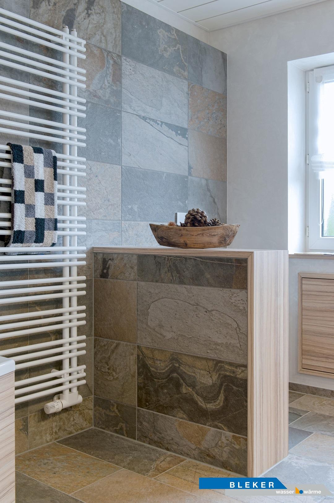 Bad mit Abmauerung Sandsteinfliesen, weisser Handtuchheizkörper