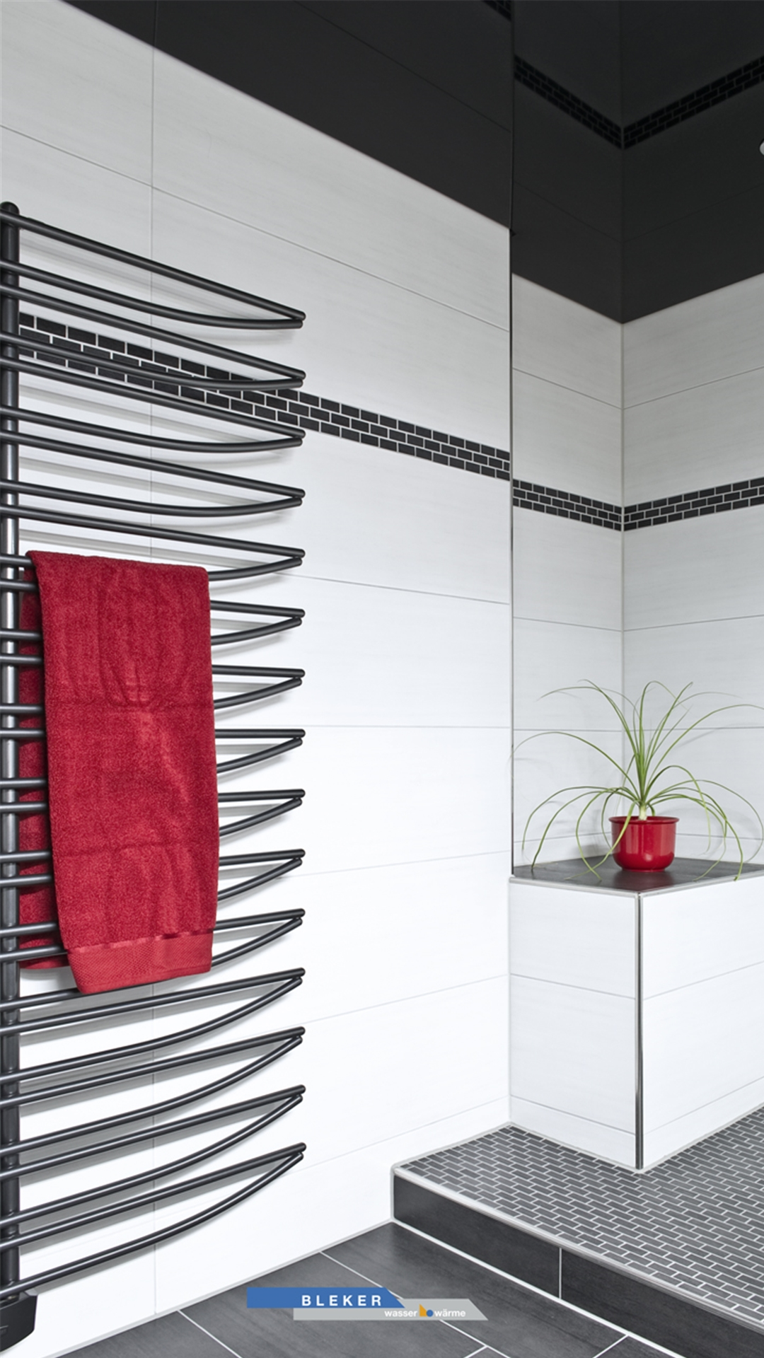 Bad in schwarz weiss mit rotem Handtuch und rotem Blumentopf