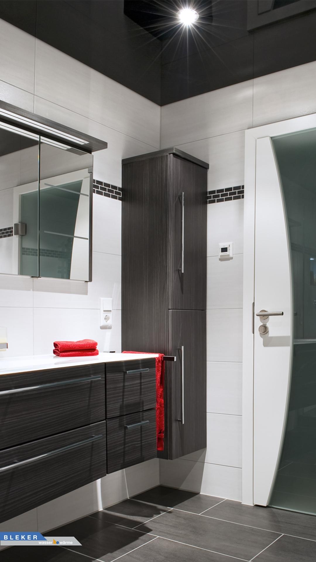Badezimmer in schwarz weiss mit roten Handtüchern