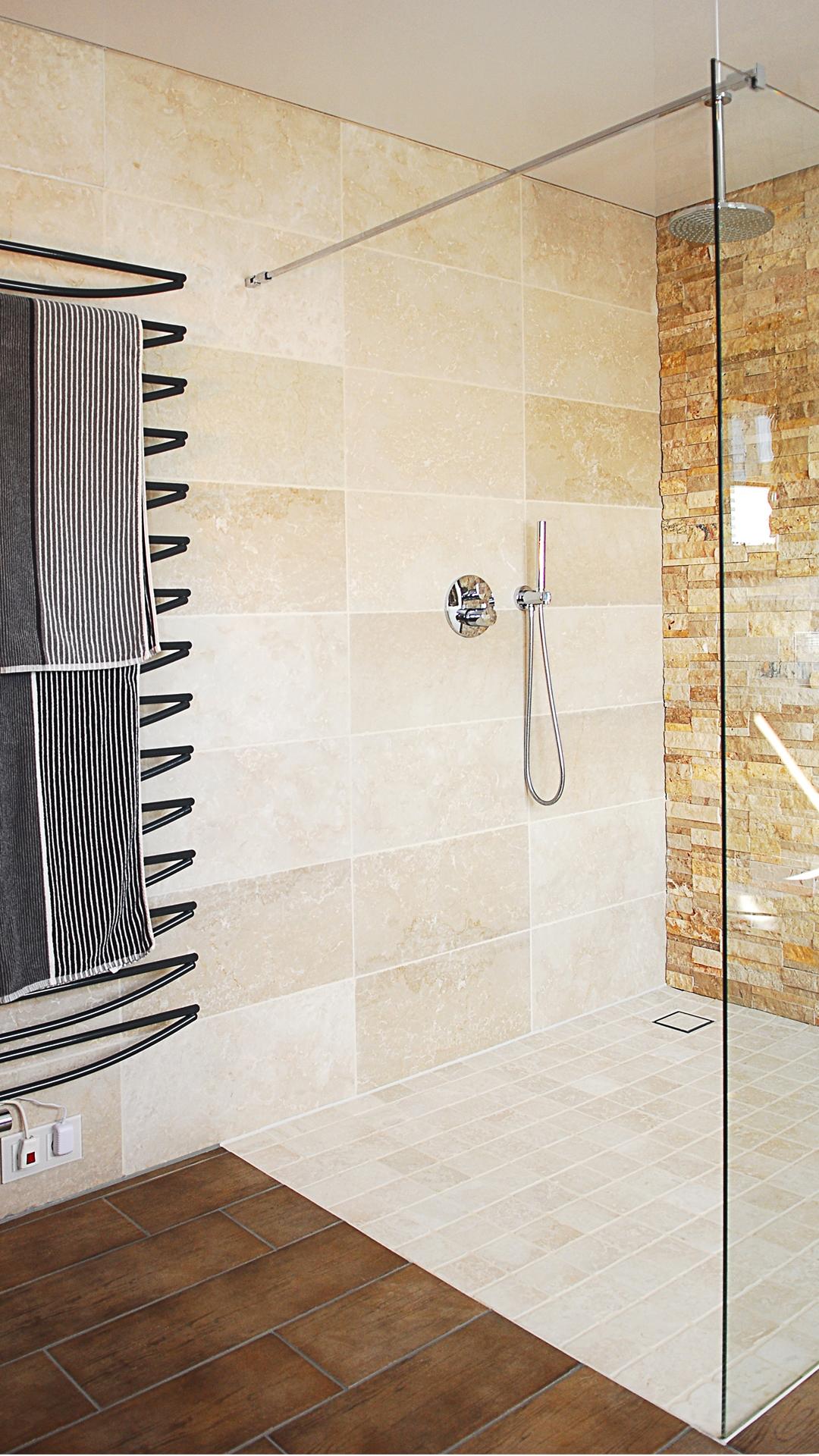 Schöne Dusche aus Naturstein mit Design-Heizkörper in Anthrazit
