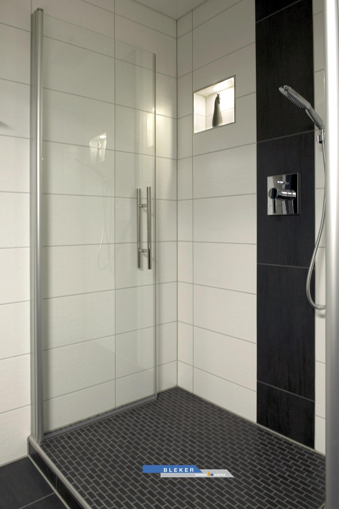 grosse breite Dusche schwarz weiss gefliest