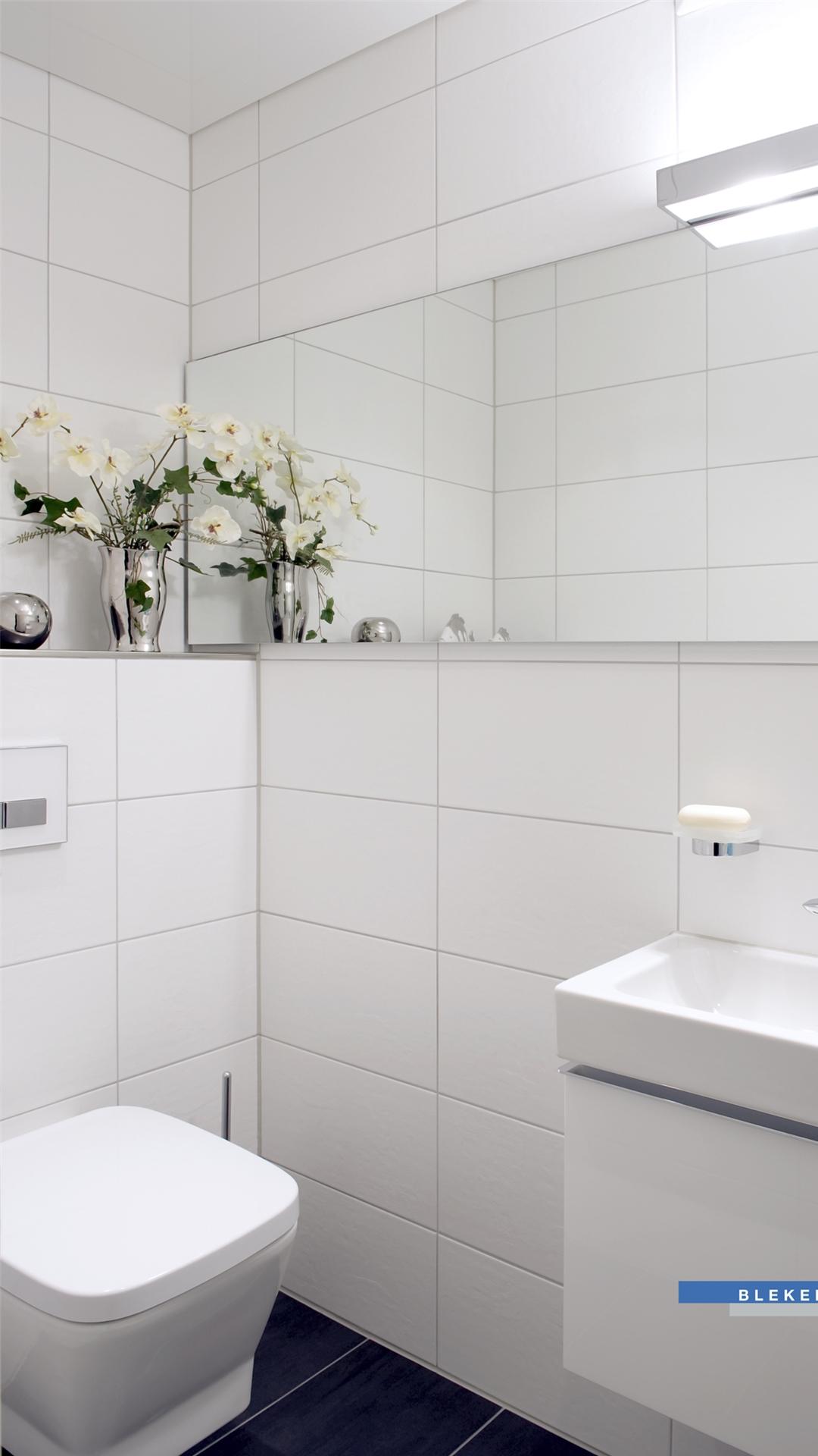 Gäste-WC in weiß mit großem Spiegel und Deko