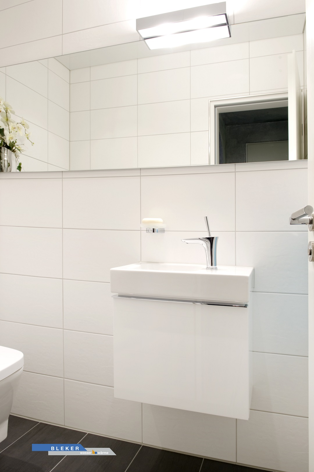 Gäste-WC mit weissem Waschtisch und grossem Spiegel