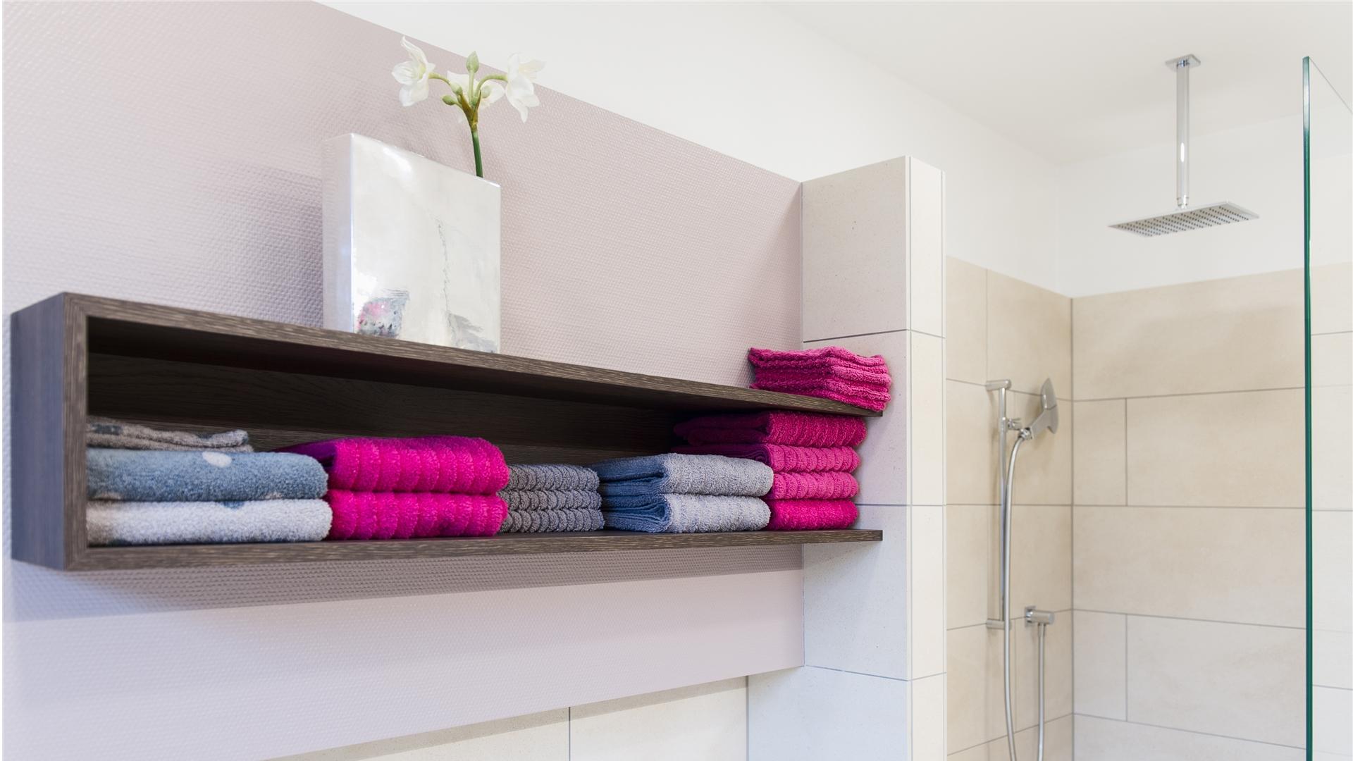 Handtuchregal in schwarzbraun mit Handtüchern in pink und grau
