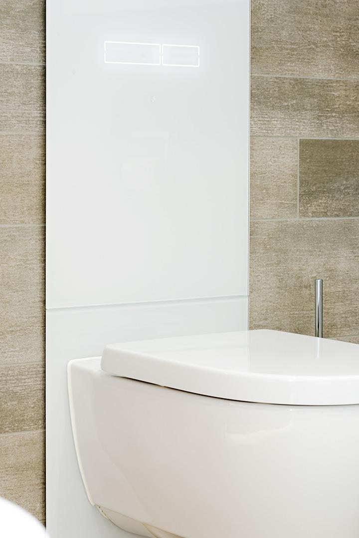 Toilette an einer Rückwand aus Glas im Badezimmer in Borken