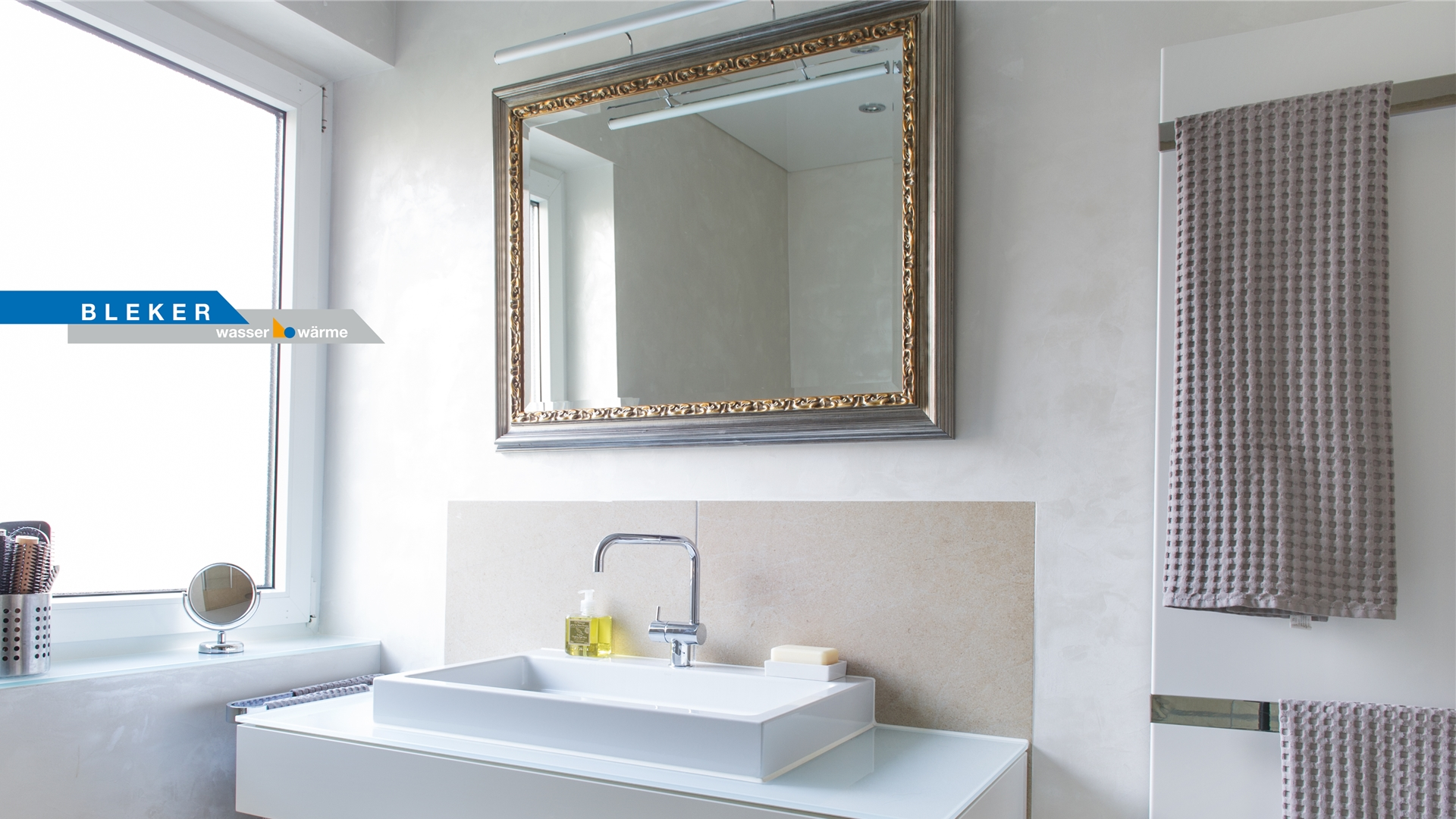 Spiegel mit goldenem Stuckrahmen über weissem Waschtisch