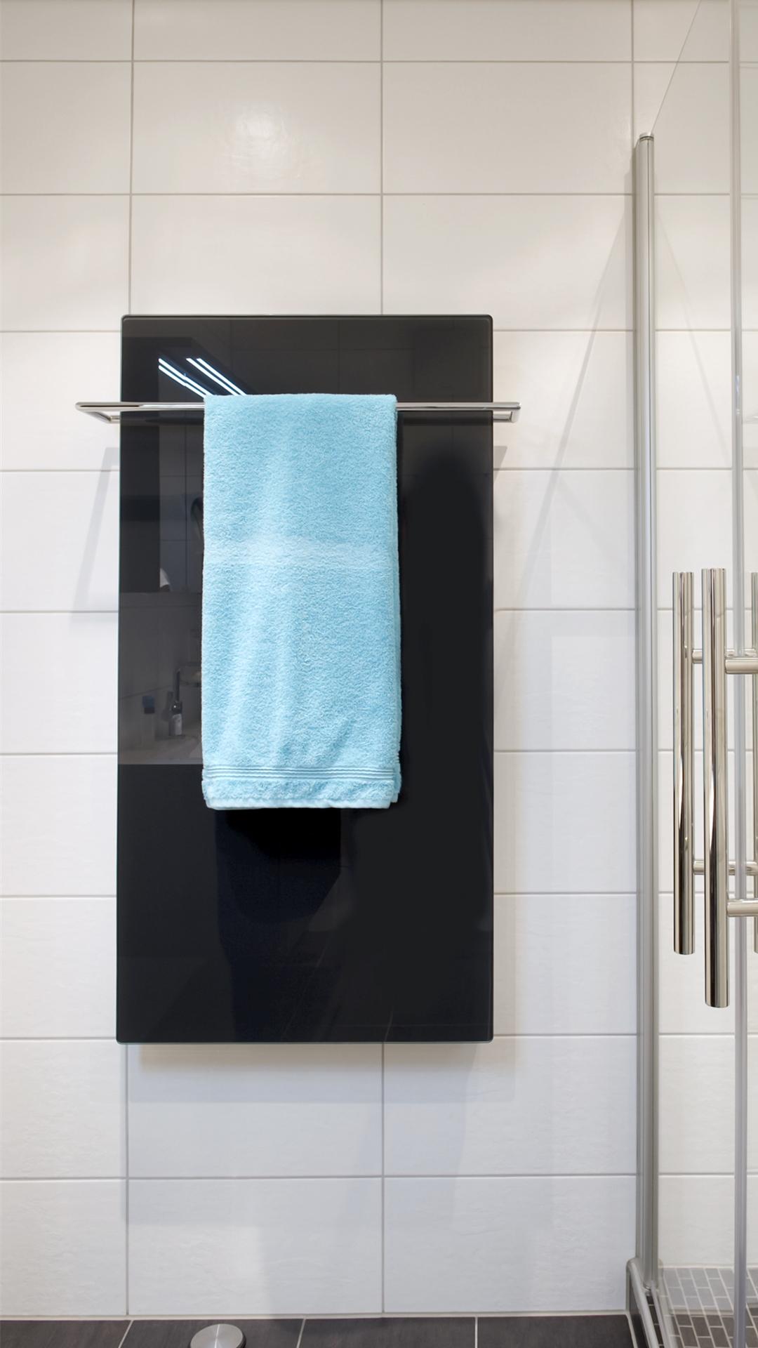 hochglänzender schwarzer Heizkörper mit türkisem Handtuch