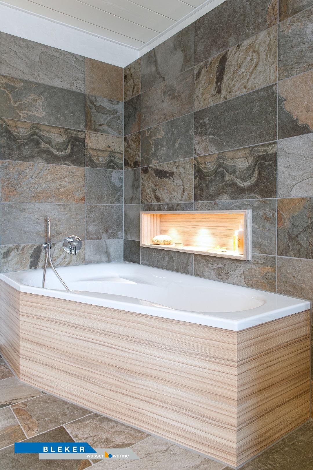 schönes Bad mit ausgefallenen Fliesen, Wanne und beleuchtetem Ablagefach in der Wand